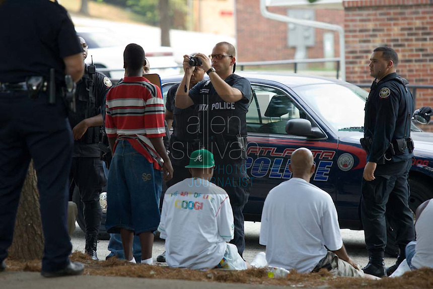 Atlanta Police Department officers speak to and photograph people detained during sweeps in the Vine City Terrace Apartments on Saturday, August 18, 2007. Police said they found drugs, drug money and at least one stolen car during the sweeps, which also included Bowen Homes.