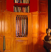A wardrobe door is fitted with a delicate wooden grille through which shirts hanging in the wardrobe are visible
