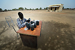 Simon Dau, a pharmacist, fills prescriptions at his desk under a tree outside the Catholic Church-sponsored clinic in Leu, a village in the contested Abyei region along the border between Sudan and South Sudan. The clinic, along with the rest of the village, was looted and burned in 2011 when soldiers and militias from the northern Republic of Sudan swept through the area, chasing out more than 100,000 Dinka Ngok residents. A few thousand families have returned since northern combatants withdrew in 2012, yet their life is precarious. In Leu, the church rehabilitated the clinic and drilled a well. For political and logistical reasons, the Catholic Church is one of the few organizations willing to openly accompany the people of Abyei during these uncertain times.