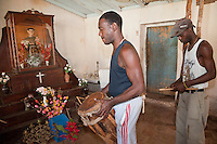 Cuba, Trinidad.  Afro-Cuban Drummer Playing in front of Shrine to Saint Anthony (San Antonio), Performing an Afro-Cuban Religious Ceremony.
