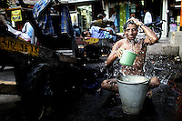 A young man washing in the streets of old Dehli, India, September 2006 Photo By Andrew Parsons/Press Association.