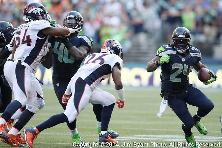 Seattle Seahawks running back Marshawn Lynch (24) looks for running room against  Denver Broncos safety Rahim Moore (26) in the fourth quarter at CenturyLink Field in Seattle, Washington on September 21, 2014.   Lynch ran for 88 yards and scored two touchdowns in the Seahawks 26-20 overtime win over the Broncos.   ©2014. Jim Bryant Photo. All rights Reserved.