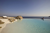 A woman relaxes on the edge of the infinity pool with a terrace that resembles the perfect beach