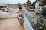 Bunroeun at home on the terrace roof of his home..A Khmer boy learns to play classical violin at the college of Beaux Arts, at the edge of Cambodia's capital, Phnom Penh. He is an orphan and comes from a poor family. His parents died long ago, from AIDS related diseases. He lives with his grandmother and his uncle, and their family. He lives on the top floor of an apartment block, where his family run a textile business, sewing together clothes and ornamental flags from around the world. A dozen young women work in this textile business, and the boy's home space is actually amidst this small factory environment which he shares with them. They eat, work and play together like an extended family or community. Phnom Penh, Cambodia