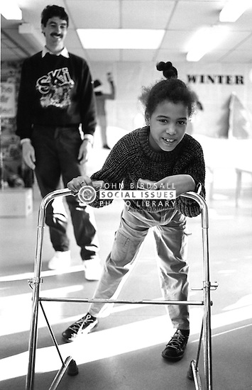 Young girl with physical impairment walking with walking frame,