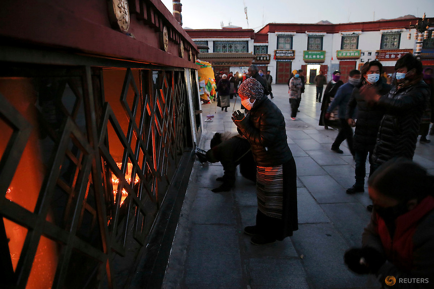 Pilgrims pray outside the Johkang Temple in central Lhasa, Tibet Autonomous Region, China at dawn November 20, 2015. Every day thousands of Tibetans visit and pray at Johkang Temple, considered one of the most sacred place of worship. REUTERS/Damir Sagolj