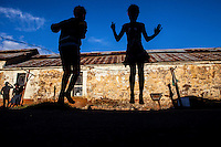 Children skip at one of Durban Deep Goldmine's old hostels on the outskirts of Johannesburg, South Africa. During the previous few weeks, all the power cables in the area were dug up and stolen, leaving the entire area without any power. Ironically, these kids are using the stolen cable casing as skipping ropes.
