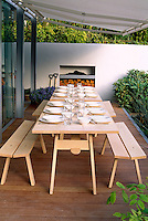 A pair of wooden trestle tables laid for lunch on a contemporary decked terrace that has the luxury of an outdoor fireplace