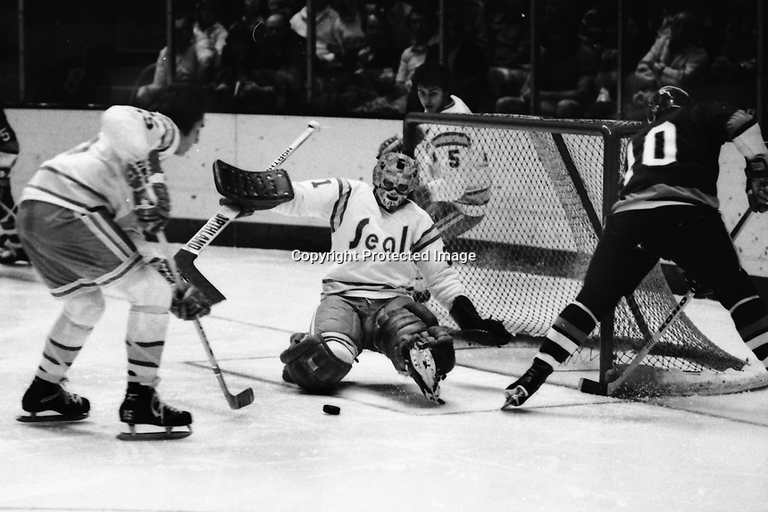 Seals goalie Gary Simmons makes save against New York Islander #10 Lorne Henning, Seals Jim Neilson.<br />(1975 photo by Ron Riesterer)