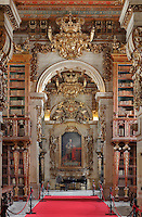 Red Room, with bookcases with Chinese motifs, lacquer and gilding by Manuel da Silva, looking through archway to the Black Room of the Joanina Library, or Biblioteca Joanina, a Baroque library built 1717-28 by Gaspar Ferreira, part of the University of Coimbra General Library, in Coimbra, Portugal. IN the Black Room is the portrait of King John V or Joao V, 1689-1750, by Domenico Dupra, 1725, topped by a gilded sculptural crown and angels. The Casa da Livraria was built during the reign of King John V or Joao V, and consists of the Green Room, Red Room and Black Room, with 250,000 books dating from the 16th - 18th centuries. The library is part of the Faculty of Law and the University is housed in the buildings of the Royal Palace of Coimbra. The building is classified as a national monument and UNESCO World Heritage Site. Picture by Manuel Cohen