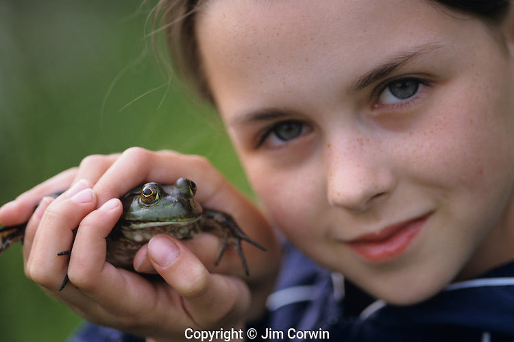 Young girl (11 yrs old) holding bull frog in hands looking into camera at park Lake Pleasant Bothell Washington State USA