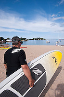 Carrying a stand up paddleboard on the Lake Superior beach at Grand Marais Michigan.