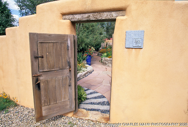 Susan Blevins of Taos, New Mexico, created an elaborate home garden featuring containers, perennial beds, a Japanese themed path and a regional style that reflectes the Spanish and pueblo architecture of the area. The granite stones of a Japanese pathway contrast with the soft adobe look of a pueblo style gate to create a unique contrast in Susan Blevin's garden.