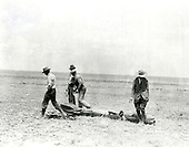 Doctor Robert H. Goddard's rocket after flight in New Mexico on April 19, 1932.  Those carrying the rocket are (left to right): Nils Ljungquist, machinist; most likely Charles Mansur, welder; Goddard's brother-in-law and machinist Albert Kisk; and Goddard. The rocket had new guiding vanes controlled by a gyroscope which helped stabilization. In 1930, with a grant from the Guggenheim Foundation, Goddard and his crew moved from Massachusetts to Roswell, New Mexico, to conduct research and perform test flights away from the public    eye. This rocket was one of many that he launched in   Roswell from 1930-1932 and from 1934-1941. Doctor Goddard has been recognized as the father of American rocketry and as one of the pioneers in the theoretical exploration of space. His dream was the conquest of the upper atmosphere and ultimately space through the use of rocket propulsion. When the United States began to prepare for the conquest of space in the 1950's, American rocket scientists began to recognize the debt owed to the New England professor. They discovered that it was virtually impossible to construct a rocket or launch a satellite without acknowledging the work of Doctor Goddard. .Credit: NASA via CNP