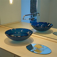 A blue glass bowl-shaped wash basin stands on a blonde wood counter in this bathroom