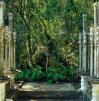 Weathered concrete columns frame the surreal remains of the pleasure garden designed by Edward James