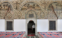 Prayer carpets and frescoes in the Et'hem Bey Mosque or Xhamia e Et'hem Beut, begun 1789 by Molla Bey and finished in 1823 by his son Haxhi Ethem Bey, great-grandson of Sulejman Pasha, Tirana, Albania. The frescoes decorating the mosque, unusual in Islamic art, depict trees, waterfalls, buildings and bridges. The mosque is listed as a Cultural Monument of Albania. Tirana was founded by the Ottomans in 1614 by Sulejman Bargjini and became the capital of Albania in 1920. Picture by Manuel Cohen