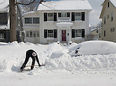 A resident digs out their car after it was buried by a snow storm and a passing plow.