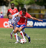 Gerardo Iraheta (17) of El Salvador collides with Kelin Angulo (15) of Costa Rica during the group stage of the CONCACAF Men's Under 17 Championship at Jarrett Park in Montego Bay, Jamaica. Costa Rica defeated El Salvador, 3-2.