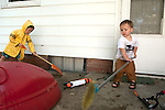 "Brothers, age four, left, and age two, right, switch to feverishly ""cleaning"" our back patio after cooling off with hose and squirt gun on a hot day."
