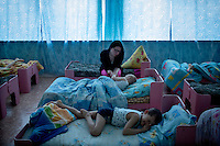 Children lie in their beds at the Solnyshko ('Little Sunshine') centre for underprivileged children in the village of Chilchi. The centre looks after orphans and children of alcoholic or ill parents. Lidia Konochenko (middle) helps Maxim Detuk get off to sleep.