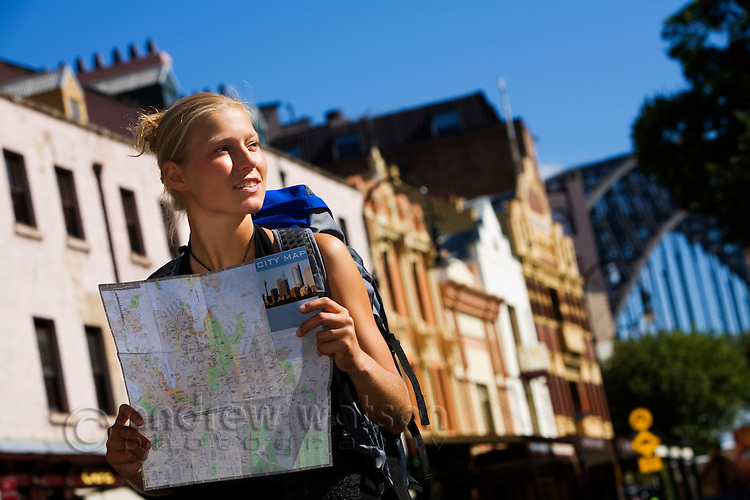 A backpacker checks her map in the streets of The Rocks district.  Sydney, New South Wales, AUSTRALIA