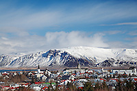 Snowy Kambshorn mountain towering above Reykjavik city skyline, Iceland