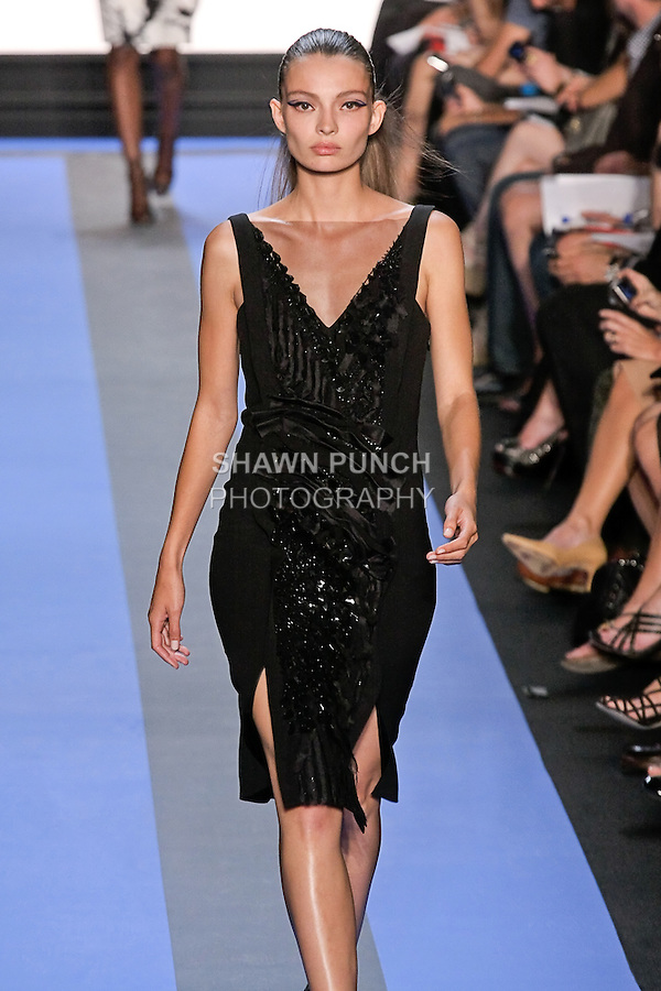 Carola walks runway in a carbon black crepe illusion v-neck embroidered cocktail dress, by Monique Lhuillier, from the Monique Lhuillier Spring 2012 collection fashion show, during Mercedes-Benz Fashion Week Spring 2012.