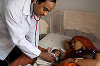 "Dr. Vikasendu Agarwal, the paediatrician of the Muradnagar Community Health Centre (CHC), checks on a newborn in the paediatrics ward of the CHC in Ghaziabad, Uttar Pradesh, India. He says that ""Bigger incentives should be given to women to have a tubectomy done after 2 children instead of the current plan of giving incentives for every child born institutionally as the in most cases,money goes directly to the household instead of the mother's healthcare defeating the very purpose of this incentive. The growth-rate between different socio-cultural population groups in the region are drastically different due to lack of awareness of the benefits of family planning in certain groups"". Photo by Suzanne Lee / Panos London"