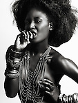 High fashion photo of a young beautiful woman with shiny black skin wearing jewelry