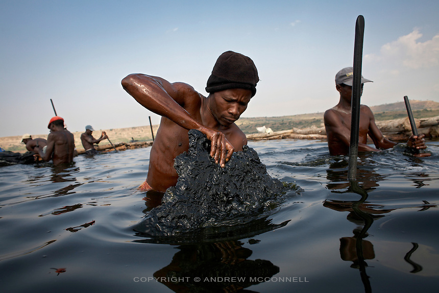Men extract rock salt from the bed of Lake Katwe, Uganda, on Saturday, Dec. 29, 2007.  The rock is extracted three days a week from the lake with workers paid by weight at approximately $2 per 100kg, of which the government takes a percenage. All men work from dusk till dawn with a strong worker extracting 400 kg per day. Skin damage is a major problem for people working at Lake Katwe as chemicals in the water eat away at any nick or cut and also cause nerve damage.
