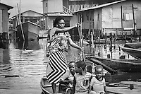 A mother backing her baby and paddling a canoe.