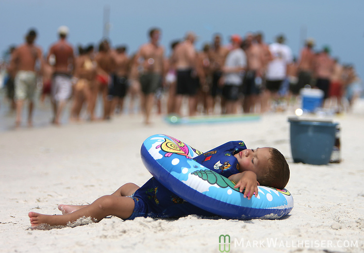"""A 2 year-old from Carrabelle, Florida takes a break from his Memorial Day weekend at the White Trash Bash on Dog Island off the coast of Carrabelle, Florida May 27, 2007.  """"We came over yesterday and camped out"""" said his mother Niki Kennedy."""