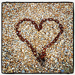 Rusty chain in the shape of a heart on beach pebbles