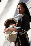 A young Native American Indian woman carrying her infant in a baby cradle