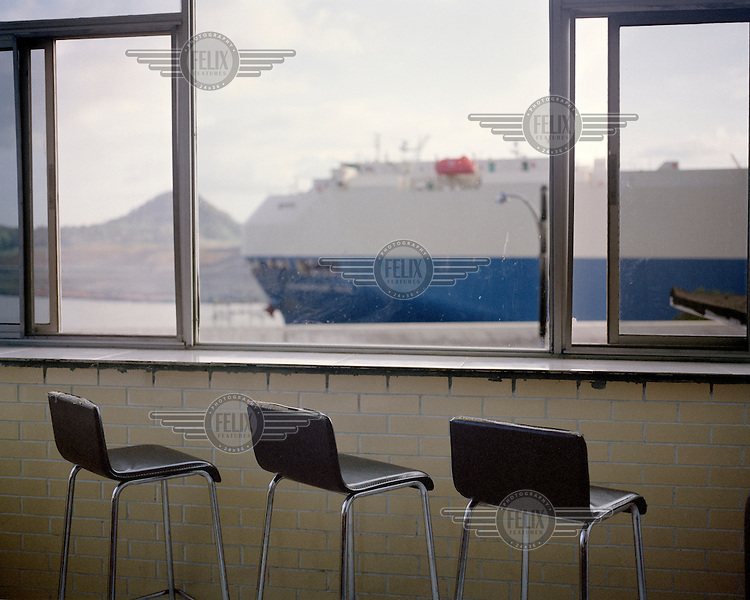 Stools in front of a window at the restaurant El Mirador del Canal (The Channel's Viewpoint). In the background a ship transits the Panama Canal.  <br /> The Panama Canal Zone is an area extending 8kms out, in each direction, from the waterway's central line, was a territory controlled by the United States between 1903 and 1979. After a 20 year period of joint administration, the Canal came under the full control of Panama in 1999. The Canal opened to shipping in 1914 and during its tenure was of great strategic importance to the US, enabling it to rapidly move its naval fleet between the Atlantic and Pacific Oceans. However, its economic value came not directly from shipping fees but from the stimulus to trade that the waterway created. One hundred years after it opened in 2014 it is due to have its locks upgraded to cater for the super sized container ships of the 21st Century.  <br /> During the era of American administration thousands of US citizens populated the Canal Zone, living and working under US law in towns built to American standards. Not all of these people returned north after the canal came under full Panamanian control many stayed on, their identities tied to the region.