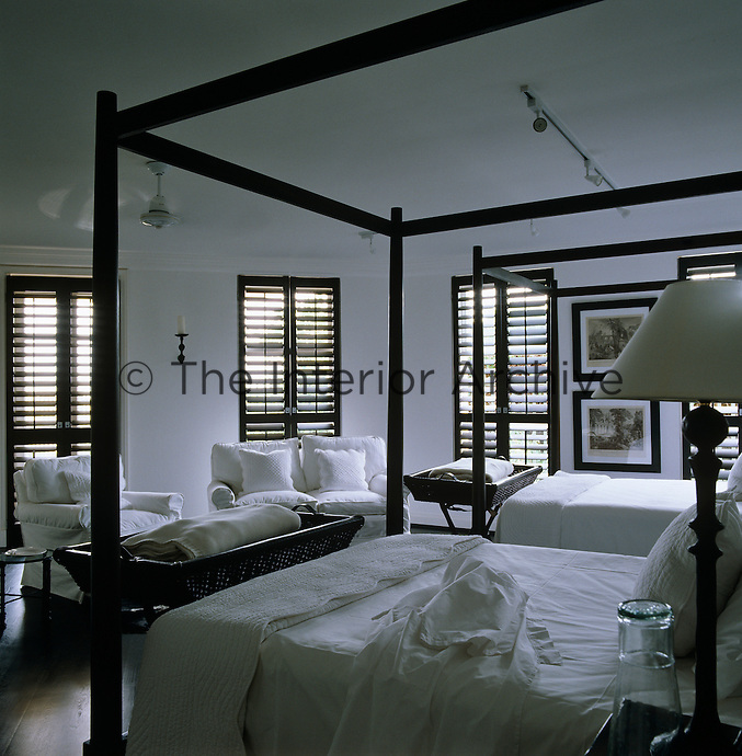 This twin bedroom is tastefully furnished with custom-designed four-poster beds and a comfortable 3-piece suite
