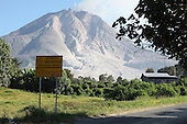 Warning sign by road approaching Sinabung Volcano, Indonesia
