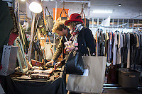 Shoppers at the trendy Brooklyn Flea, which has moved indoors for the winter into a cavernous space in Williamsburg in Brooklyn in New York, seen on opening day, Saturday, November 30, 2013. The flea market is now combined with its food market Smorgasburg in the space for the season.  Shoppers and foodies come from all over the city for the bargains, one-of-a-kind local merchandise and the locavore food that is offered for sale. (© Richard B. Levine)