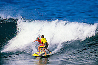 Gary 'Kong' Elkerton (AUS) and Michael Ho (HAW) clash on a wave during the running of the 1990 Pipeline Masters. Elkerton was in the running for the World Title and so was Ho's younger brother Derek Ho (HAW). Elkerton needed to advance from the heat to keep his world title hopes alive but the judges deemed the clash was a 'double interference ' and both Elkerton and Ho were eliminated from the  Pipeline Masters held at the Banzai Pipeline on the North Shore of Oahu, Hawaii. Elkerton finished runner up in the World Title to Tom Curren (USA) with Derek Ho finishing rated #8  Photo: joliphotos.com