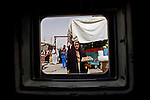 Iraqi civilians stare at a passing U.S. Army Humvee as the unit patrols a commercial district of Abu Ghraib, July 9, 2007