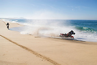 Female motorcycle rider crashing in water on beach, Baja, Mexico