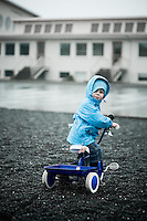 A little boy on his blue tricicle in the rain in a school yard.