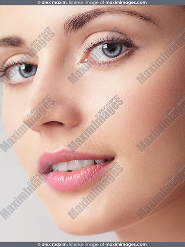 Closeup beauty portrait of a young woman face with clean natural makeup, smooth skin and blue eyes