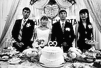 Kazakhstan. Aralsk. Kazak wedding. The muslim bride wears a white wedding dress while the groom has a black suit and a tie. The new couple stands up with on both sides their witnesses (best man (L) and woman (R)). Food and cakes with a plastic heart on the table. Aralsk is located in the Kyzyl Orda Province. © 2008 Didier Ruef ..