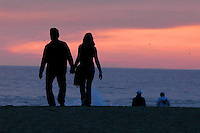 A couple walk hand-in-hand towards the sunset at the shoreline of Santa Monica Beach on Sunday, December 27, 2009.