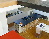 A view of the kitchen from the upper level reveals a central island used as a breakfast bar and a white dining table