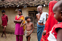 "(L-R) Amit (13), Dharma (18, soon to be married), Akanksha (8), Tribhuvan Adivasi (50), Kelaji Adivasi (45), and Vinita's (23, married when 14, has 3 children) baby. Tribhuvan, a farm labourer, says that ""it was a mistake to have so many children. Food is difficult for us."" Kelaji and Tribhuvan have a total of 6 children and live in poverty in Baul ka Dhera hamlet, Mugari Village, Allahabad, Uttar Pradesh, India. Allahabad, a poorer district of the state of Uttar Pradesh, is the most populated district of the most populous state of India. While Ghaziabad, located close to India's capital city, Delhi, has a population of 4,661,452 with a sex ratio of 878 girls against every 1000 boys, and a high literary percentage of 85%, Allahabad, has a population of 5,959,798 and a sex ratio of 902 girls against every 1000 boys and a literacy rate of 74.41%. Photo by Suzanne Lee / Panos London"