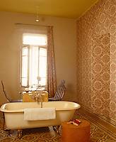 One wall of this high-ceilinged bathroom has been covered in wallpaper in which several cupboard doors are concealed