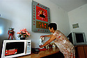 7/15/2005--Nanjie Village, Henan Province, China..Wang Fenghua, 60, cleans her Mao statue in her free apartment given to her by Nanjie village, a model communist village in the central province of Henan. The village collectivised its agricultural production and industry in the mid 1980s - when the rest of the country was doing the opposite, introducing market reforms put forward by former leader Deng Xiaoping. ..It continues to be run on Maoist egalitarian lines and has become something of a tourist attraction because of its staunch adherence to the values of the past. ..Photograph By Stuart Isett.All photographs ©2005 Stuart Isett.All rights reserved.